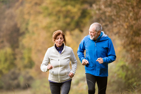 Photo for Beautiful active senior couple running together outside in sunny autumn forest - Royalty Free Image