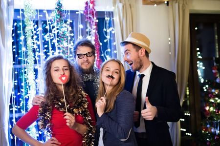 Foto de Beautiful hipster friends with photobooth props celebrating the end of the year, having party on New Years Eve, chain of lights behind them. - Imagen libre de derechos