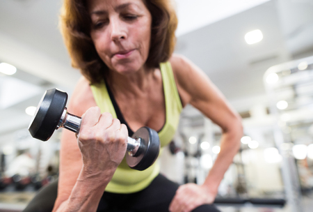 Photo pour Senior woman in gym working out with weights. - image libre de droit