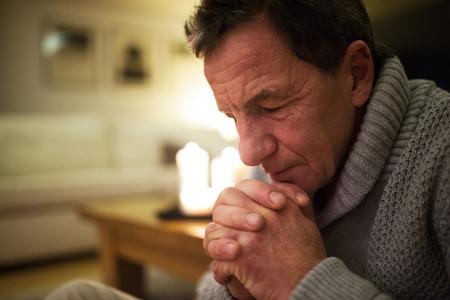 Photo for Senior man at home praying, burning candles behind him. - Royalty Free Image