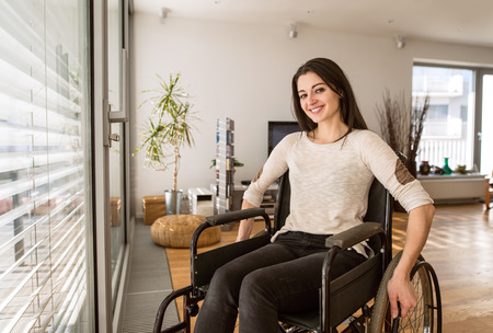 Photo pour Young disabled woman in wheelchair at home in living room. - image libre de droit