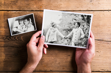 Foto de Hands holding pictures of senior couple. Studio shot, woo - Imagen libre de derechos