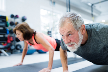 Foto de Senior couple in gym working out, doing push ups - Imagen libre de derechos