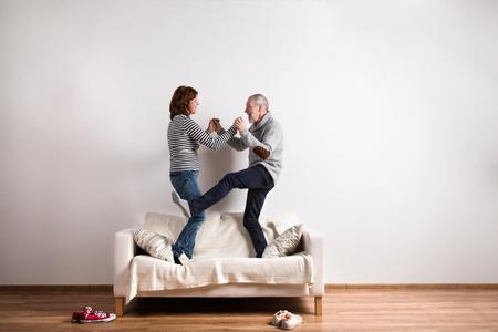 Photo pour Beautiful senior couple standing on couch, dancing. Studio shot. - image libre de droit