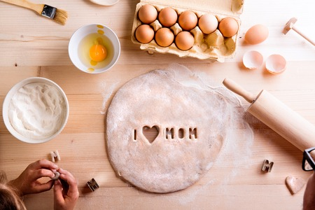 Photo for Mothers day composition. Hands of unrecognizable girl baking cookies, playing with dough. I love Mom sign made with cookie cutter. Studio shot on wooden background. - Royalty Free Image