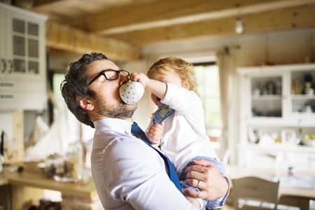 Foto de Businessman holding little son in the arms, drinking coffee. - Imagen libre de derechos