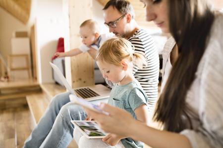 Foto de Young parents with little children and gadgets at home. - Imagen libre de derechos