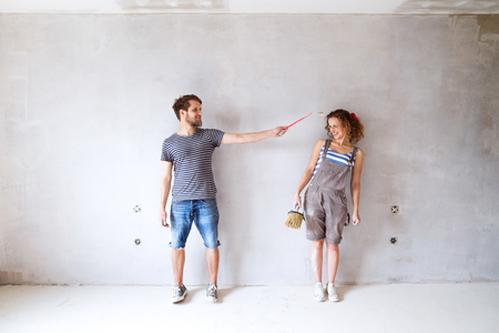 Photo for Young couple in love painting walls in their new home. - Royalty Free Image