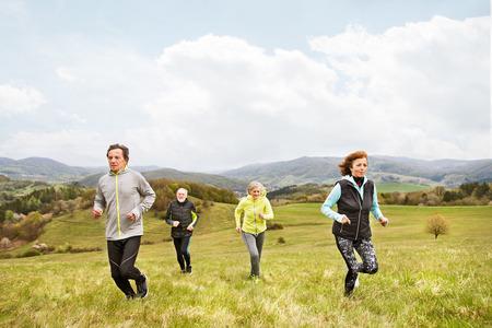 Photo pour Group of seniors running outside on green hills. - image libre de droit