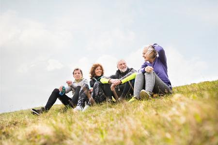 Foto de Group of senior runners outdoors, resting and talking. - Imagen libre de derechos