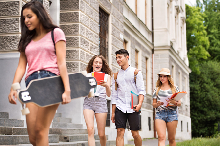 Photo pour Group of attractive teenage students walking to university. - image libre de droit
