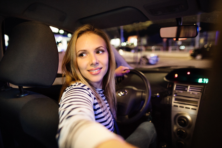 Foto de Beautiful young woman driving her car at night. - Imagen libre de derechos