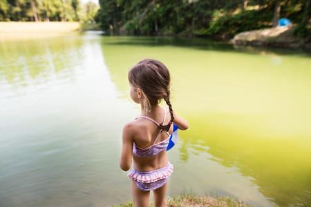 Foto de Little girl standing at the lake. Sunny summer. - Imagen libre de derechos