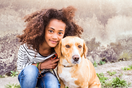 Foto de African american girl with her dog against concrete wall. - Imagen libre de derechos