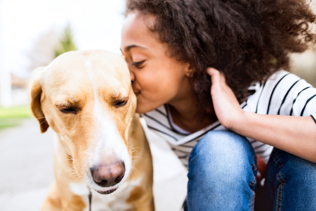 Photo for African american girl outdoors with her dog, kissing him. - Royalty Free Image