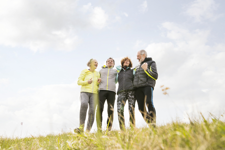 Photo for Group of senior runners outdoors, resting, holding around arms. - Royalty Free Image