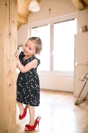 Foto de Cute little girl in dress and red high heels at home. - Imagen libre de derechos