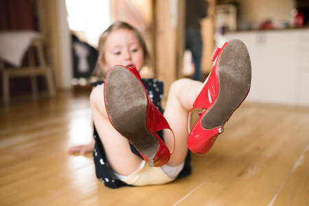 Photo pour Little girl in dress and red high heels at home. - image libre de droit