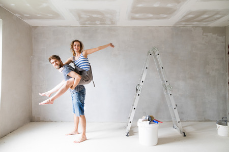 Photo pour Young couple painting walls in their new house. - image libre de droit