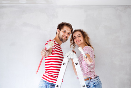 Photo for Young couple painting walls in their new house. - Royalty Free Image