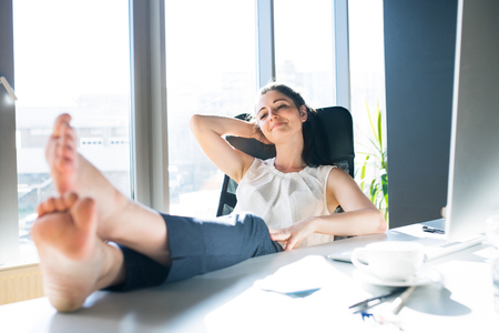 Photo pour Businesswoman in her office sitting with legs on desk. - image libre de droit