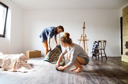Foto de Young couple moving in new house, rolling out carpet. - Imagen libre de derechos