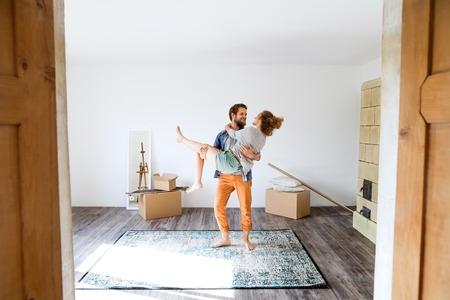 Foto de Man carrying woman in his arms, moving in new house. - Imagen libre de derechos