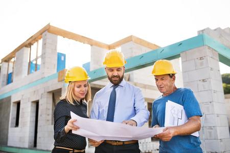 Foto de Architects and worker at the construction site. - Imagen libre de derechos