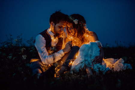 Foto de Beautiful bride and groom on a meadow at night. - Imagen libre de derechos
