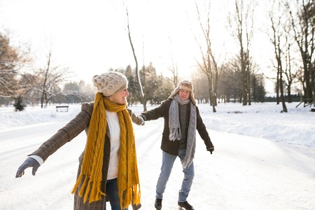 Photo for Senior couple in sunny winter nature ice skating. - Royalty Free Image