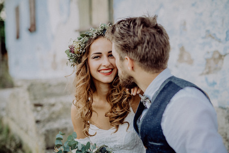 Photo pour Beautiful bride and groom in front of old shabby house. - image libre de droit