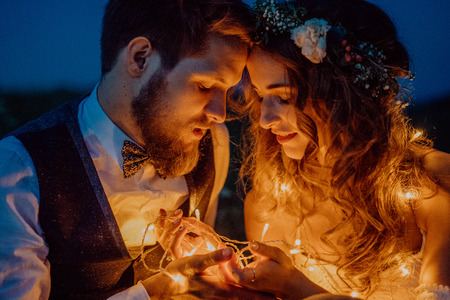 Photo pour Beautiful bride and groom on a meadow at night. - image libre de droit