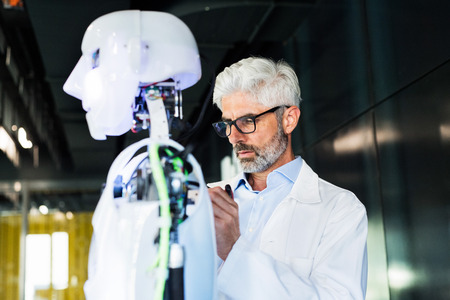Foto de Businessman or a scientist with a robot. - Imagen libre de derechos
