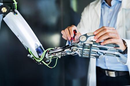 Foto de Unrecognizable scientist with a robot. - Imagen libre de derechos