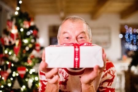 Foto de Senior man in front of Christmas tree holding a gift. - Imagen libre de derechos