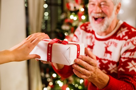 Photo pour Senior man in front of Christmas tree holding a gift. - image libre de droit