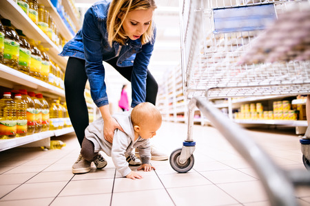 Photo pour Young mother with her little baby boy at the supermarket. - image libre de droit