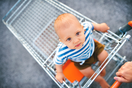 Photo for Baby boy sitting in the shopping trolley outside. - Royalty Free Image