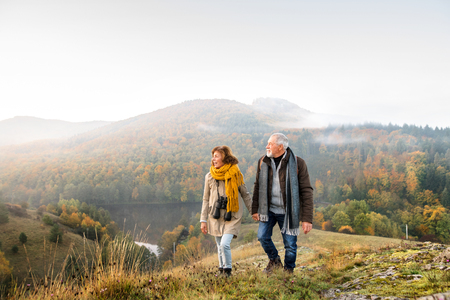 Photo pour Senior couple on a walk in an autumn nature. - image libre de droit