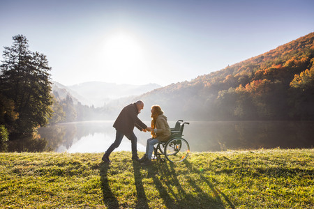 Photo for Senior couple with wheelchair in autumn nature. - Royalty Free Image