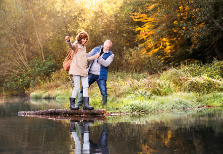Photo for Senior couple on a walk in autumn nature. - Royalty Free Image