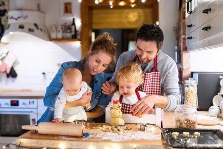 Foto de Young family making cookies at home. - Imagen libre de derechos