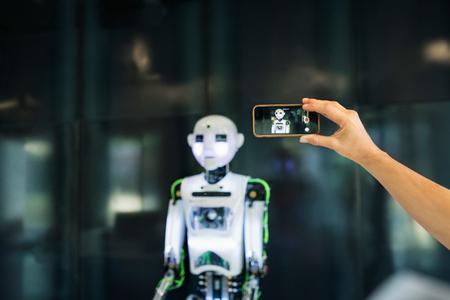 Foto de Unrecognizable scientist with smartphone and a robot. - Imagen libre de derechos