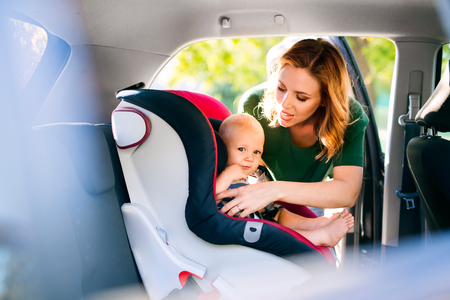 Photo for Young mother putting baby boy in the car seat. - Royalty Free Image