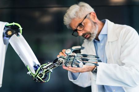 Foto de Mature businessman or scientist with a robot. - Imagen libre de derechos