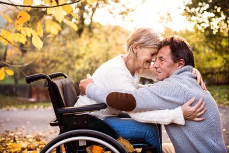 Photo pour Senior couple in wheelchair in autumn nature. - image libre de droit