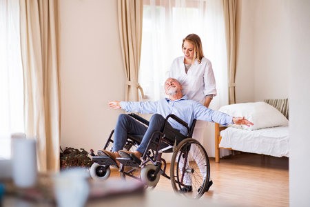 Foto de Nurse and senior man in wheelchair during home visit. - Imagen libre de derechos