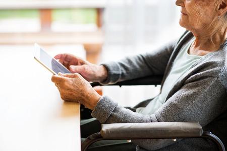 Photo pour Unrecognizable senior woman in a wheelchair with tablet at home. - image libre de droit