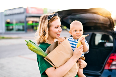 Photo pour Young mother with baby boy in front of a supermarket. - image libre de droit