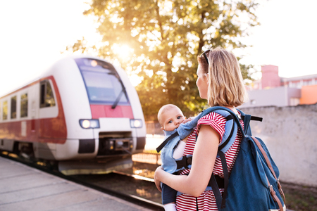 Photo pour Young mother travelling with baby by train. - image libre de droit